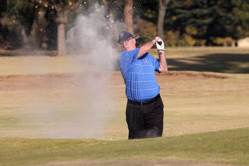 Golfer hitting a shot out of a bunker